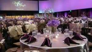 tables being set for a wedding in the ballroom at infinity park event center