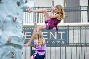 kids climbing on a climbing wall at an outdoor event at Infinity Park